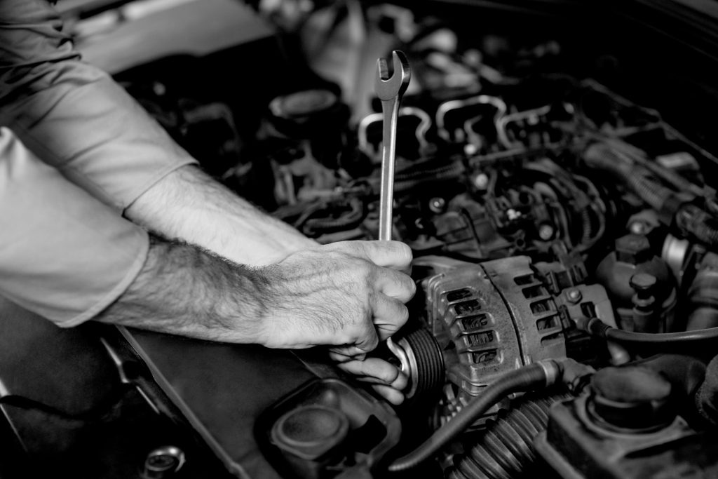 Hands of mechanic servicing a car in repair garage