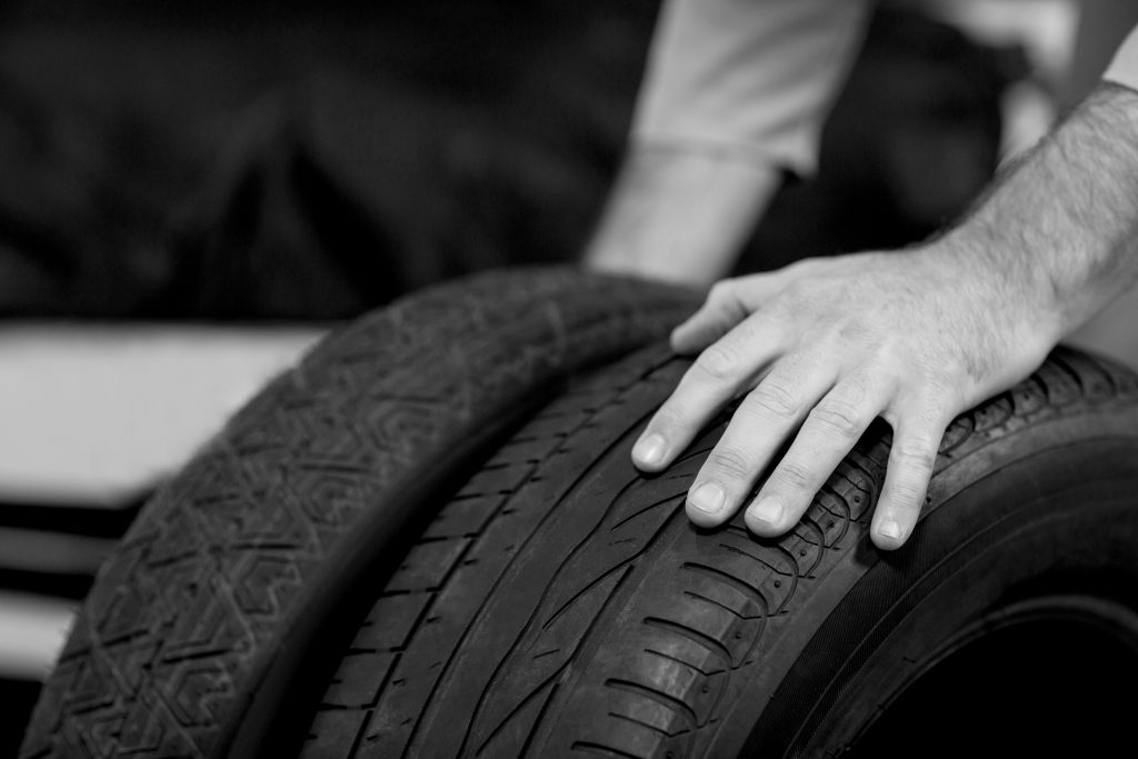 Hands of mechanic touching tyres in repair garage